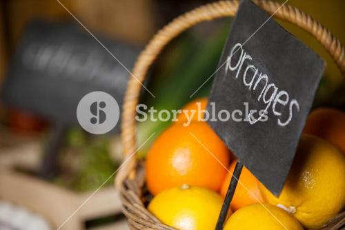 Close-up of fresh oranges in wicker basket with placard