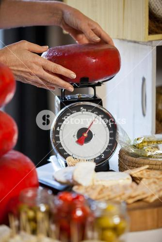 Hands of female staff weighing gouda cheese at counter