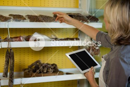 Female staff maintain records of meat on digital tablet at counter