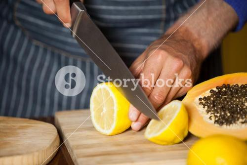 Mid-section of male staff cutting lemon in organic section