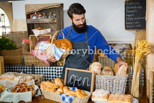 Male staff picking up bread from a wicker basket at counter