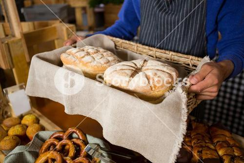 Mid section of staff holding wicker basket of breads at counter