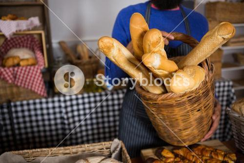 Mid section of staff holding wicker basket of french breads at counter