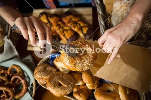 Mid section of staff packing doughnut in paper bag at counter