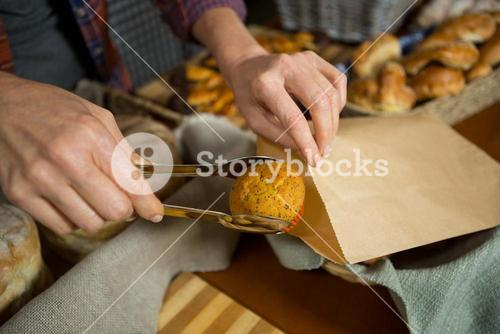 Mid section of staff packing cup cake in paper bag at counter