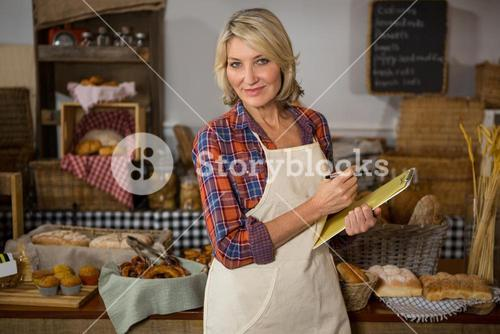 Portrait of smiling female staff writing on clipboard at bread counter