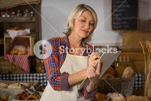 Smiling female staff writing on clipboard at bread counter