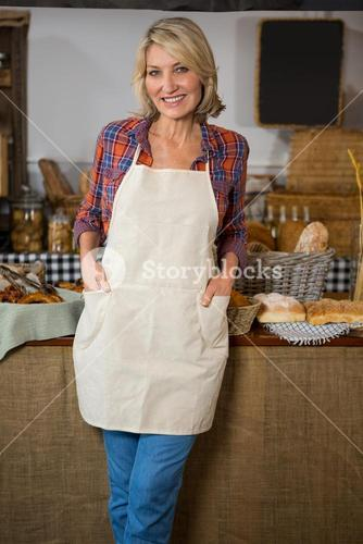 Portrait of smiling female staff standing with hands in pocket at counter