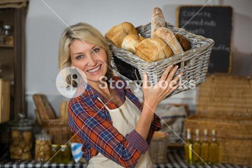 Portrait of smiling female staff carrying wicker basket of various breads at counter