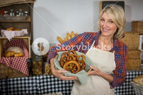 Smiling female staff holding wicker basket of pretzel bread at counter