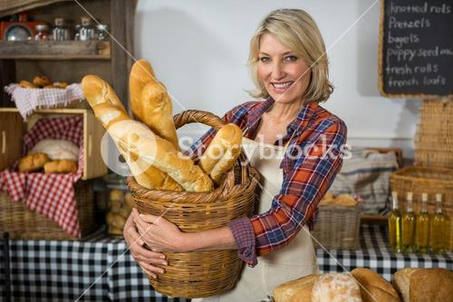 Smiling female staff holding wicker basket of french breads at counter