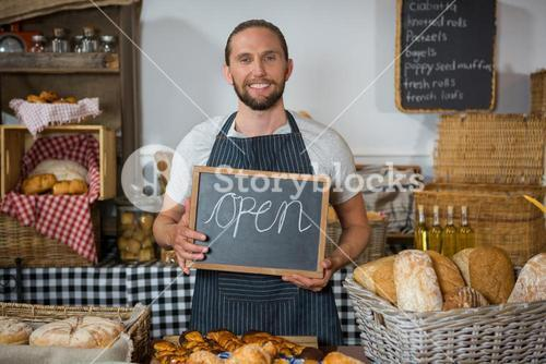 Portrait of smiling staff holding chalkboard with open sign at counter