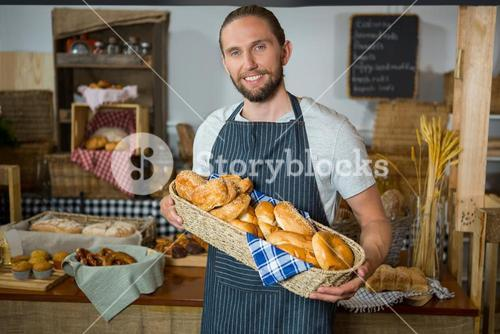 Smiling male staff holding wicker basket of various breads at counter