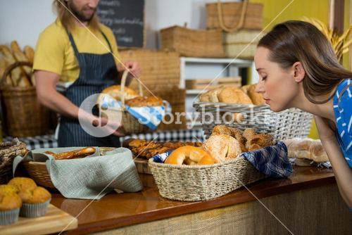 Woman smelling a breads at counter