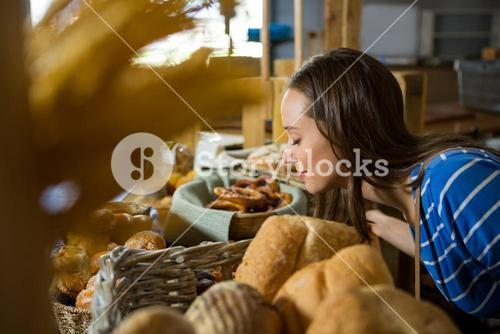 Smiling woman smelling a bakery snacks at counter