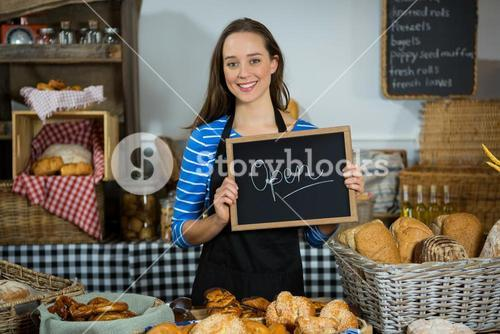 Portrait of smiling female staff holding chalkboard with open sign at counter