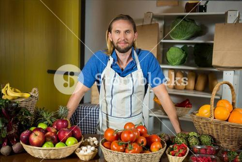 Male staff standing near vegetable counter at organic section in market