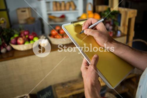 Staff writing on clipboard at organic section