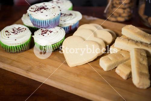 Cookies and cupcake on wooden board