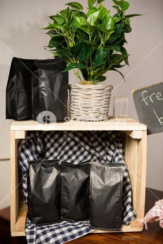 Coffee bags and pot plant on wooden table