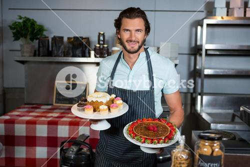 Portrait of male staff holding dessert on cake stand at counter