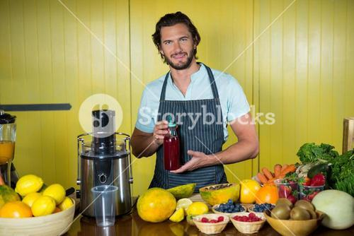 Portrait of smiling male staff holding juice bottle at counter