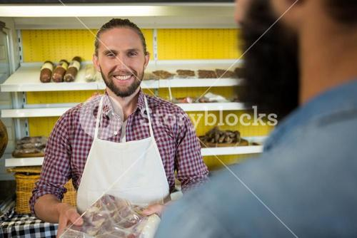 Portrait of smiling male staff holding a meat packet at counter