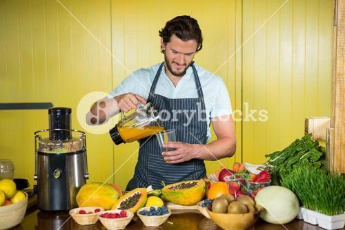 Male staff pouring juice into glass at counter