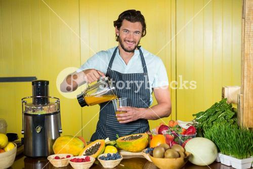 Smiling male staff pouring juice into glass at counter