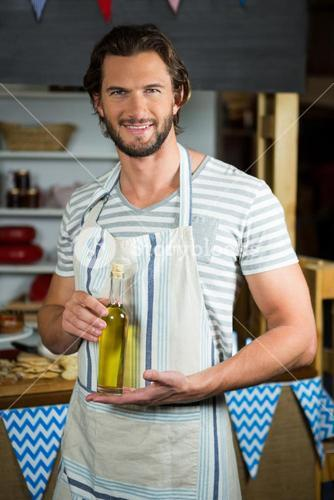 Smiling shop assistant holding olive oil bottle