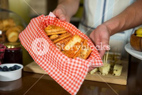 Staff holding tray of rusk at counter