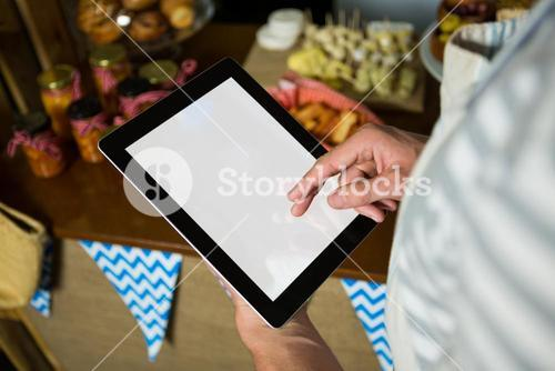 Staff using digital tablet in grocery shop