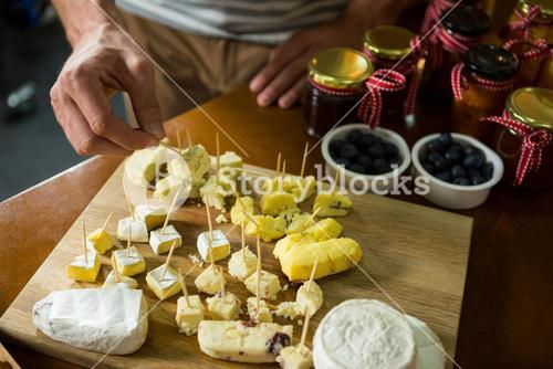 Staff arranging piece of cheese on wooden board in grocery shop