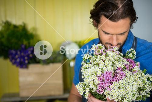 Florist holding bunch of flower in florist shop