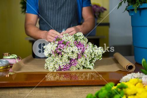 Male florist preparing a flower bouquet