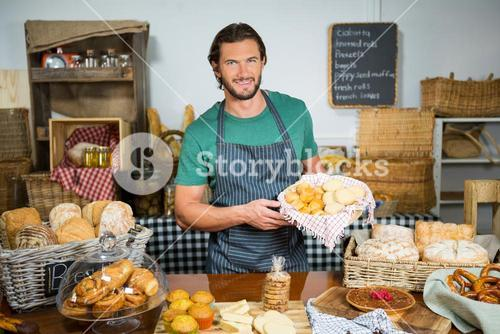 Staff holding bakery snacks at counter
