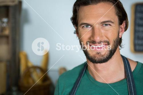 Smiling male staff standing in bakery shop