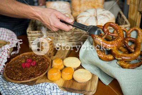 Staff holding pretzel with tong in bakery shop