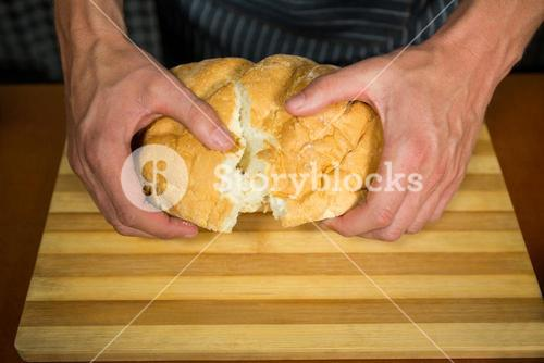 Male staff tearing a bun in bakery shop