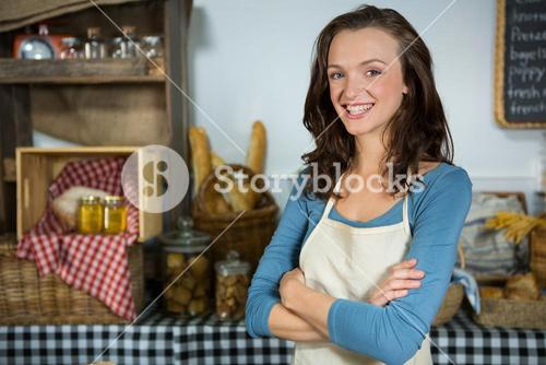 Portrait of smiling female staff standing with hands crossed