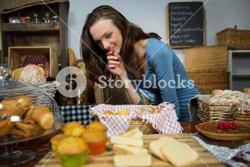 Excited woman purchasing sweet food at bakery counter