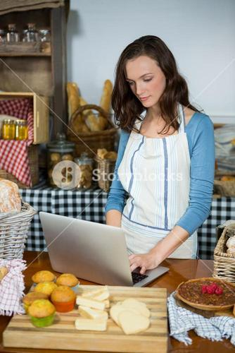 Attentive staff using laptop at bakery counter