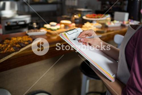 Mid-section of staff maintaining records on clipboard
