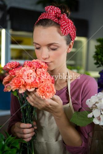 Female florist smelling a bunch of flower