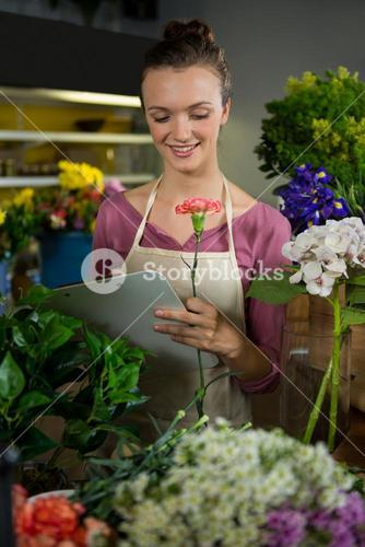 Female florist maintaining record on clipboard