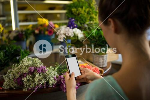 Woman taking photograph of flower bouquet
