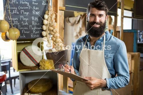 Salesman writing on clipboard at counter in grocery shop in market