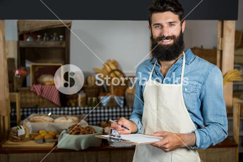 Salesman writing on clipboard at counter in grocery shop