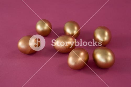 Golden Easter eggs on pink background
