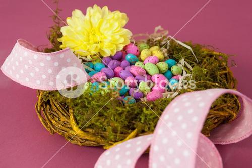 Colorful easter eggs in wicker basket with a flower